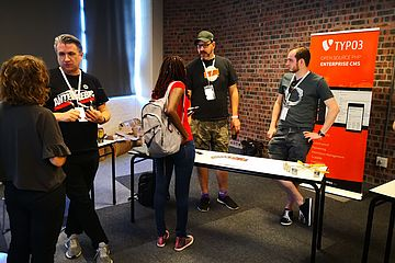 Groups of people in conversation with TYPO3-branded roll-up in the background.