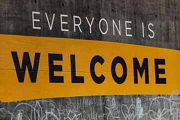 """Everyone is Welcome"" painted on a wall."