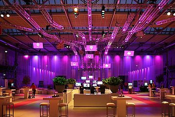 Convention center lounge with stools and tables. Magento light and computer screens in background.