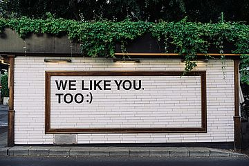 """We like you too"" written on a wall in all caps."