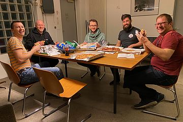 Five men sitting around a table eating pizza and looking happy.