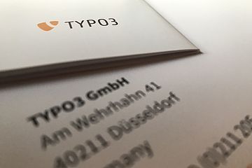 Printed paper showing the TYPO3 logo and the TYPO3 Gmbh address blurred.